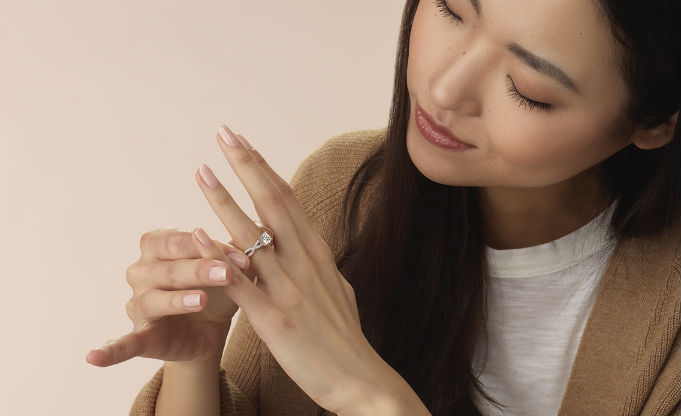 woman sliding engagement ring on her finger