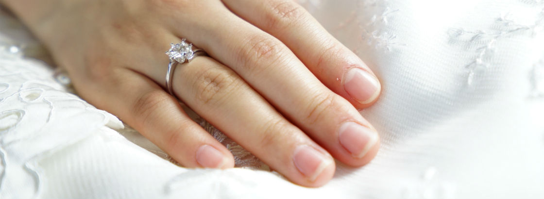 womans hand wearing ring with a 2 carat diamond