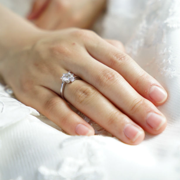 womans hands wearing ring with a 2 carat diamond