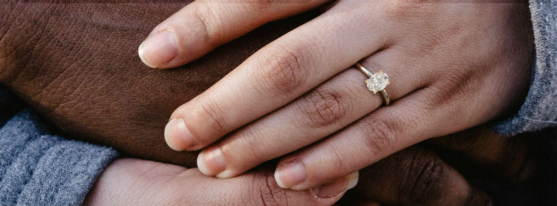couple holding hands woman wearing oval solitaire engagement ring