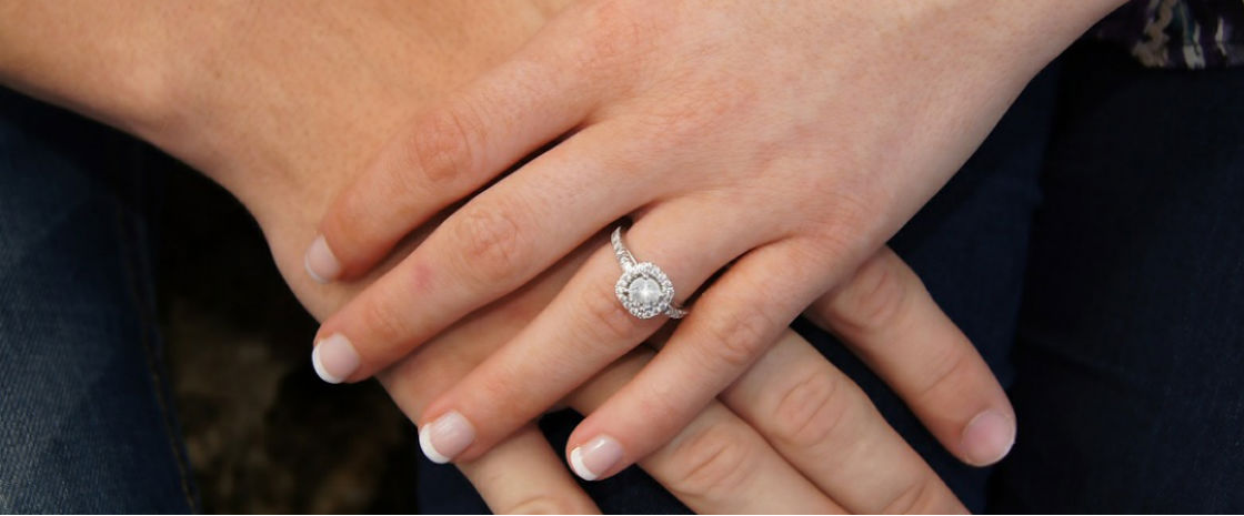 couples hands woman wearing cushion halo ring