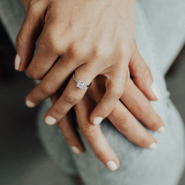 womans hands wearing emerald cut engagement ring