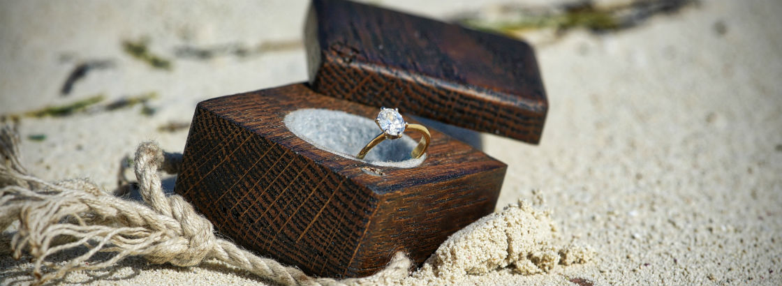 oval engagement ring in box on the beach