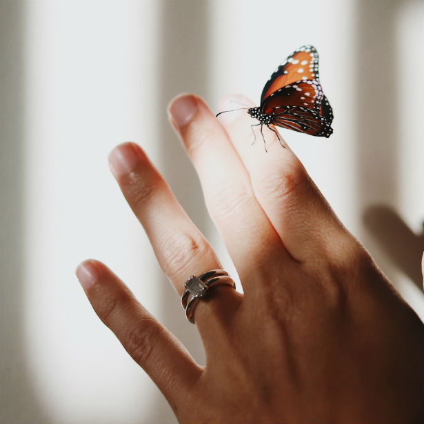 radiant cut engagement ring on woman's hand with butterfly