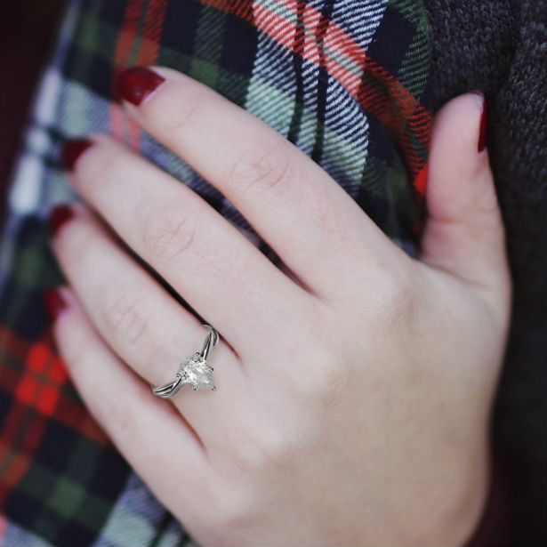 woman's hand wearing a teardrop engagement ring