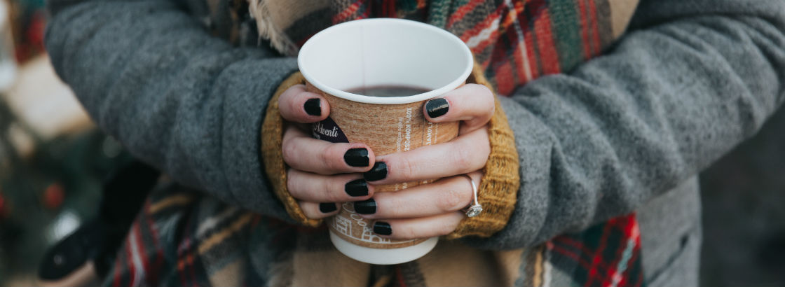woman holding coffee cup wearing cushion cut engagement ring