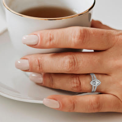 woman holding cup wearing marquise engagement ring