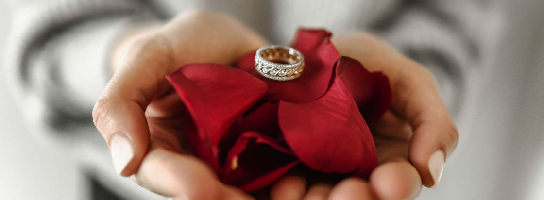 woman holding rose petals and diamond ring