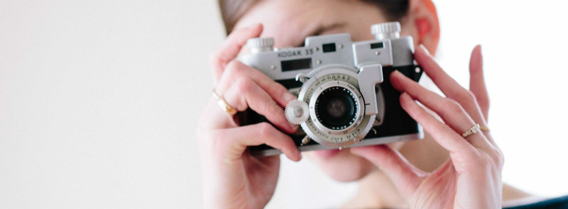 woman wearing antique style engagement ring holding camera