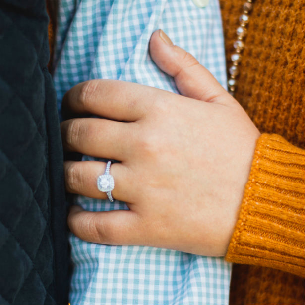 woman wearing square halo engagement ring holding man's arm
