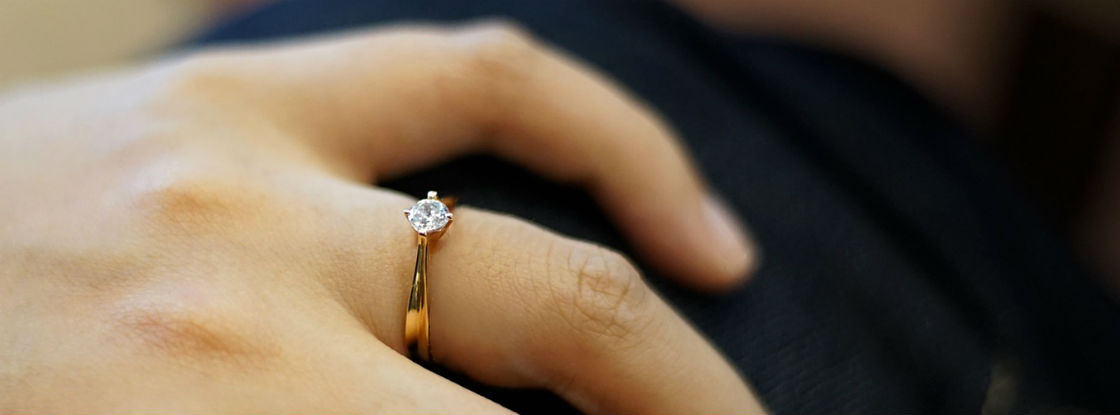 woman's hand wearing cute engagement ring