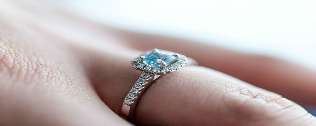 woman's hand wearing a square cut engagement ring