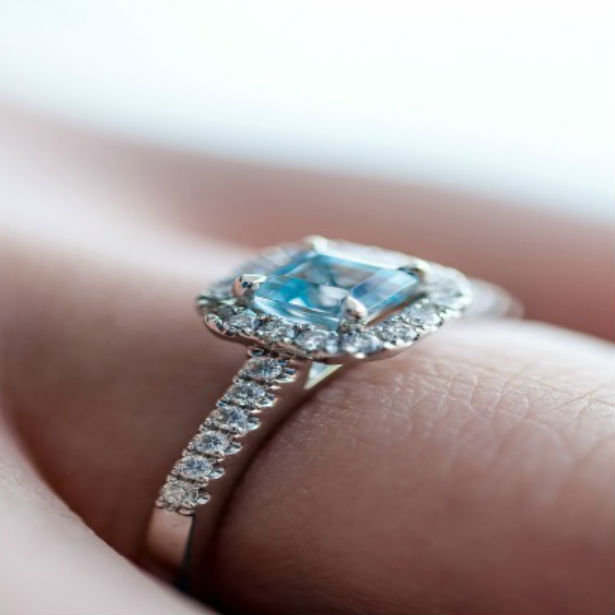 woman's hand wearing square cut engagement ring