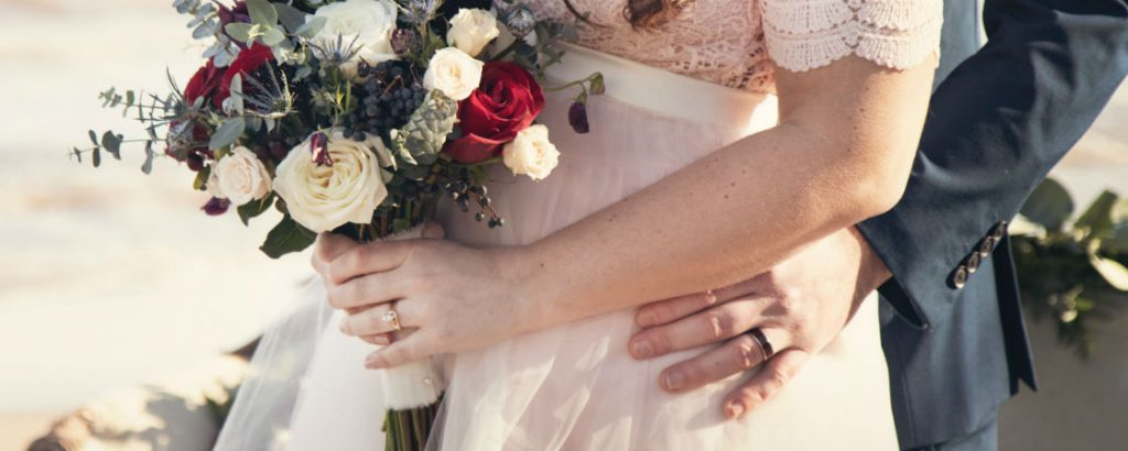 bride holding bouquet wearing yellow gold pear shaped engagement ring