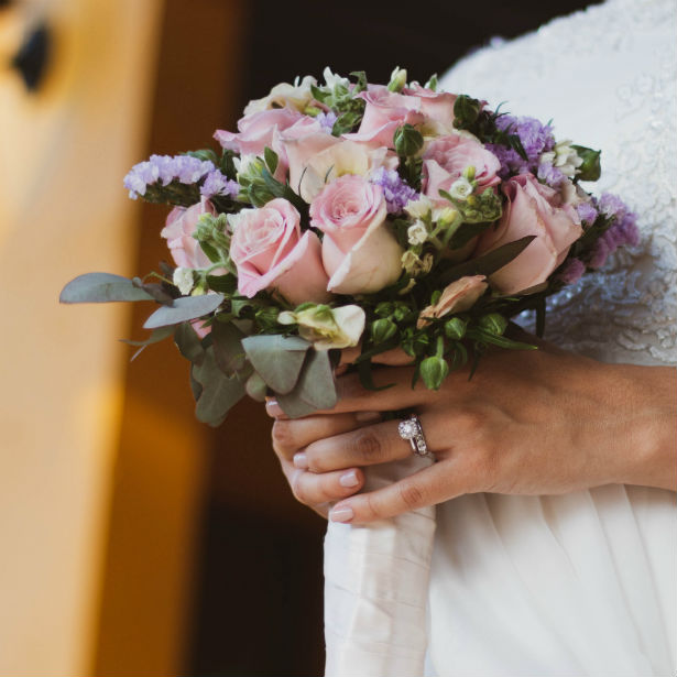 bride wearing 1 carat diamond ring holding bouquet