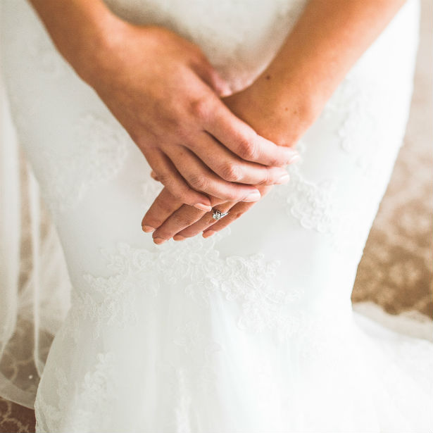 brides hands crossed wearing engagement ring