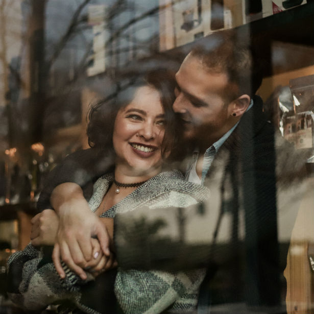couple embracing in window