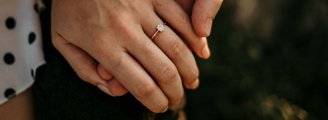 couple holding hands with women's rose gold engagement ring