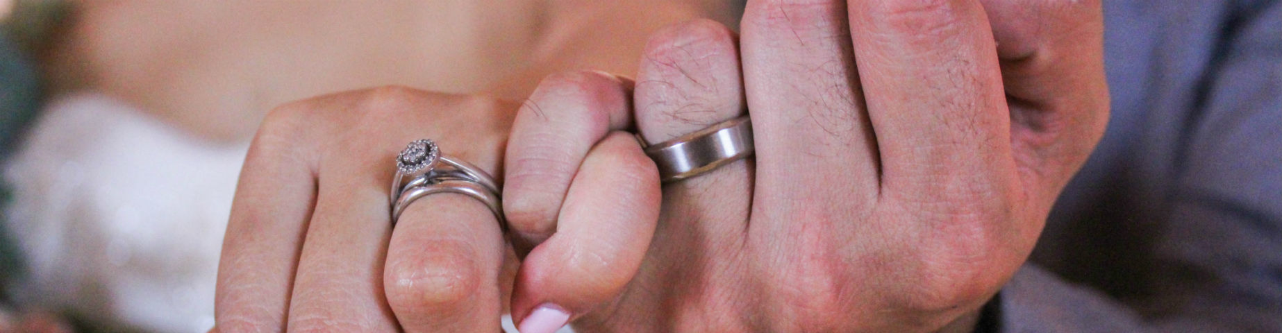 couple linking pinkies woman wearing halo engagement ring