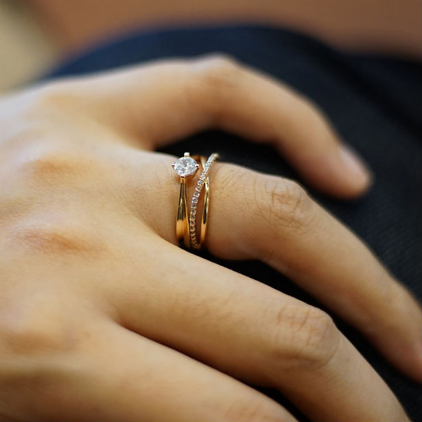 woman's hand wearing gold engagement ring with one carat diamond