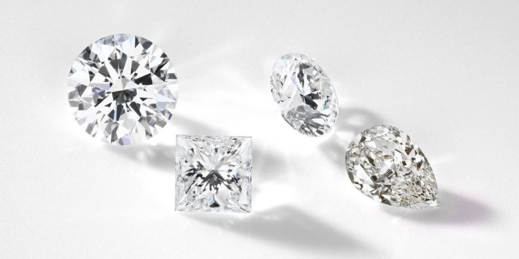 four loose diamonds that have come with diamond certificates