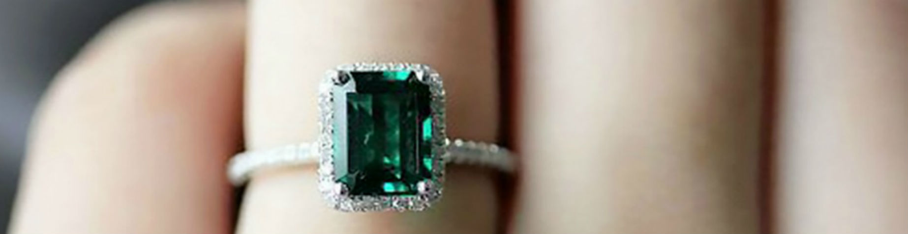 emerald engagement ring on woman's finger