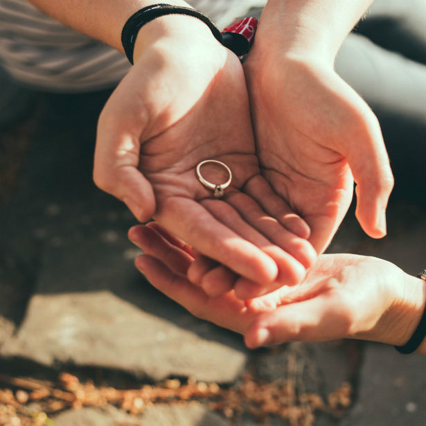 man holding engagement ring in cupped hands