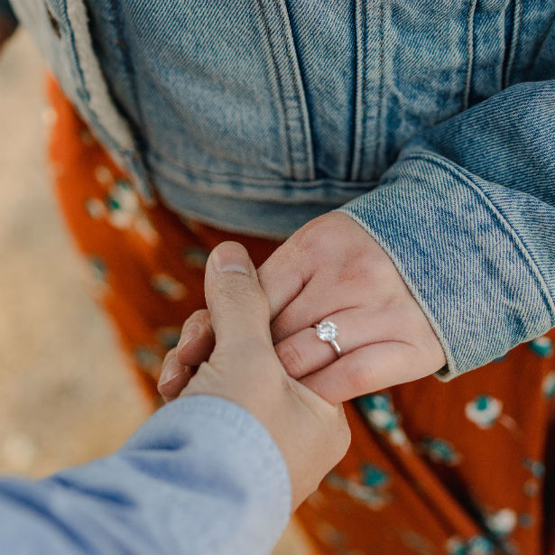 man holding woman's hand wearing 6 prong round engagement ring