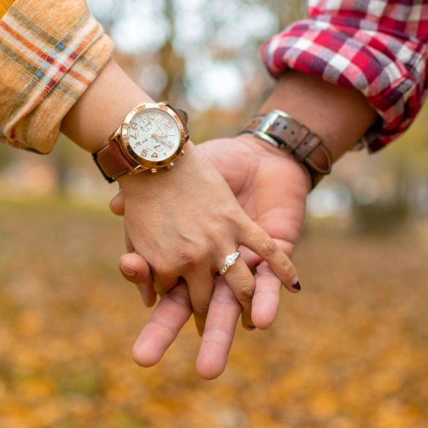 man holding woman's hand wearing channel set engagement ring
