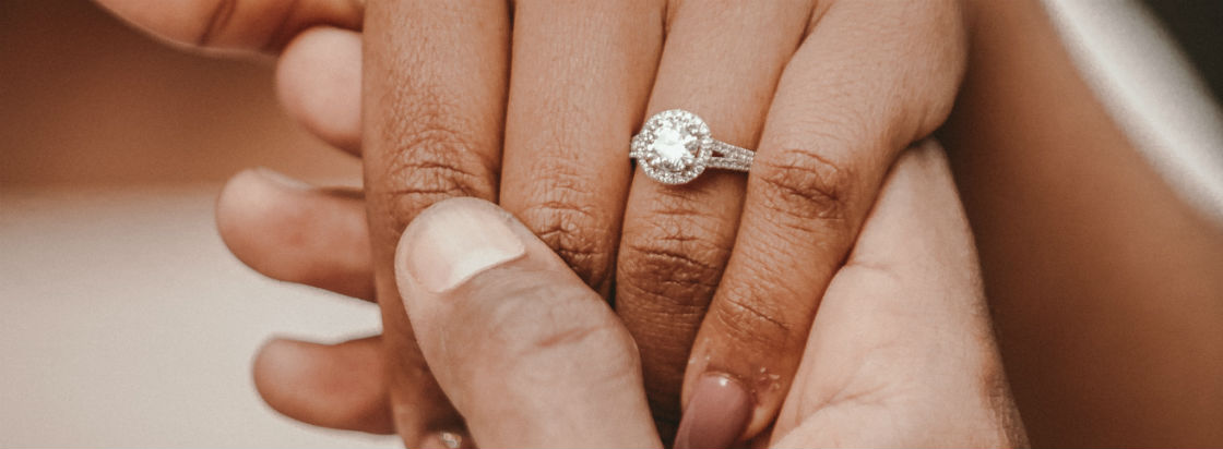 man holding woman's hand who's wearing a split shank halo engagement ring