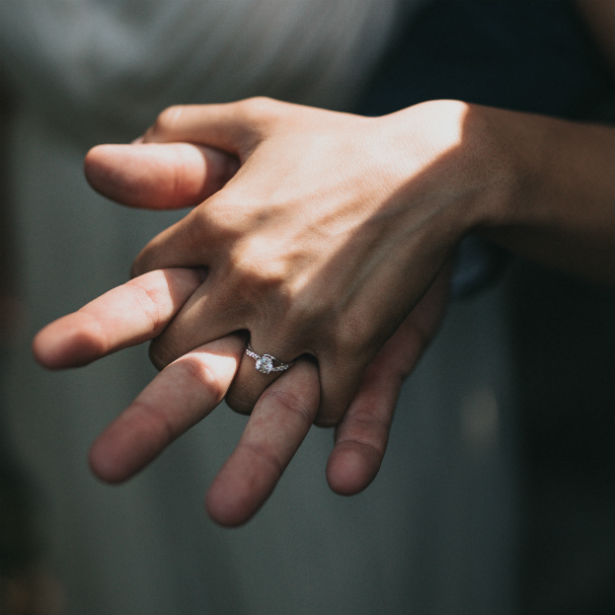couple holding hands with woman wearing engagement ring