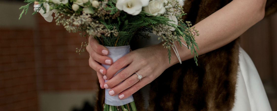 woman holding bouquet wearing thin band engagement ring