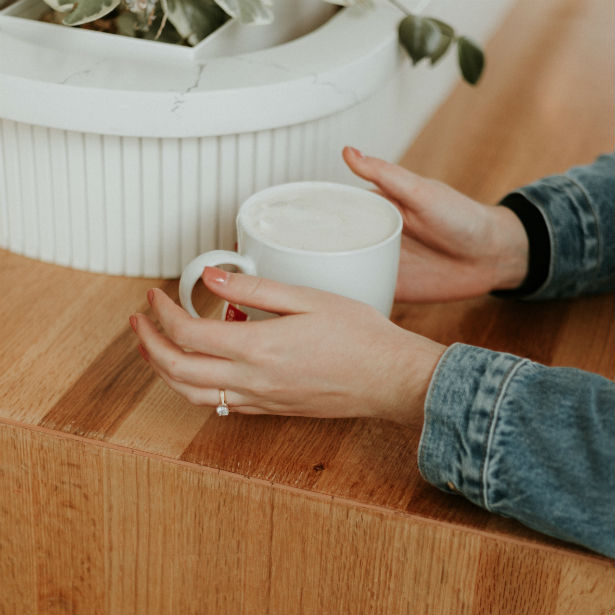woman holding coffee cup wearing yellow gold cushion cut engagement ring