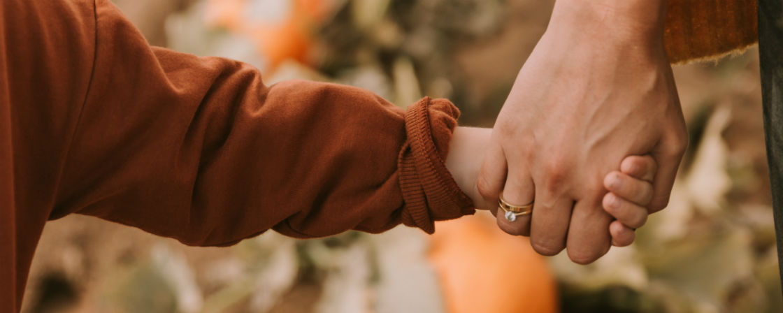 woman holding kid's hand wearing yellow gold engagement ring