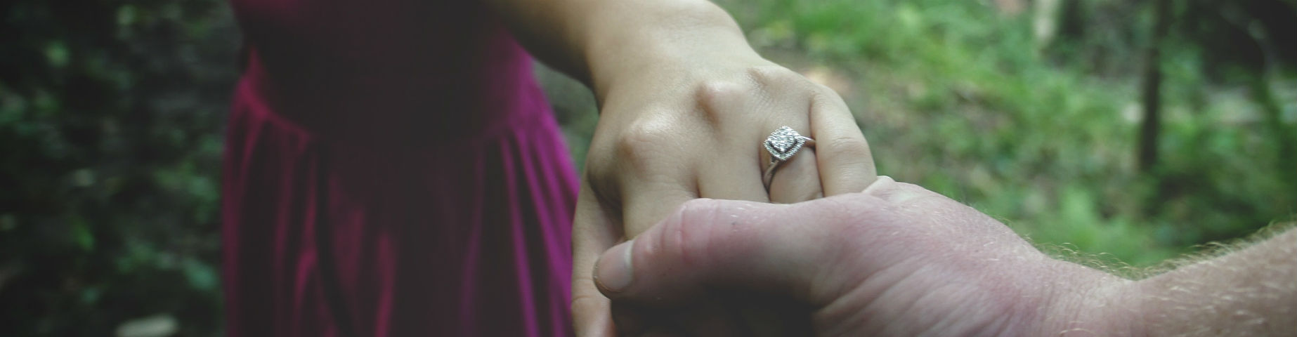 woman holding man's hand and wearing engagement ring