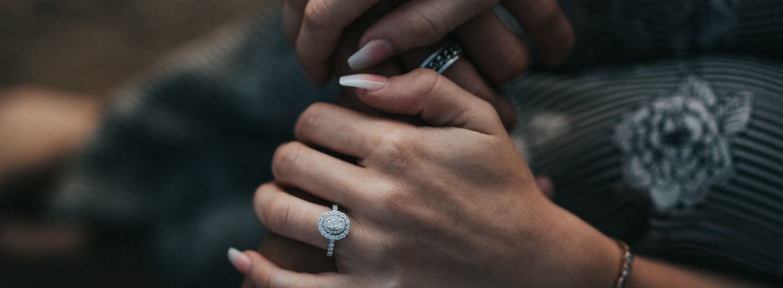 woman holding man's hand wearing big engagement ring
