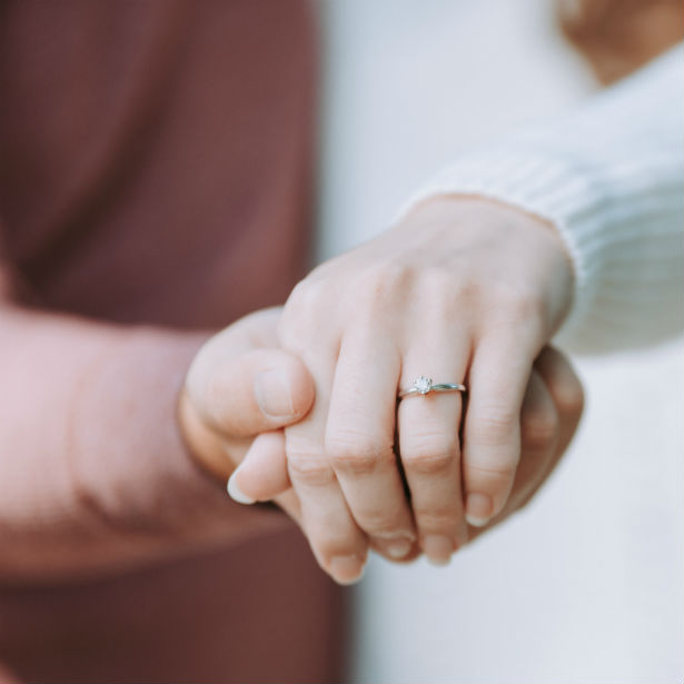 woman holding out hand wearing diamond engagement ring