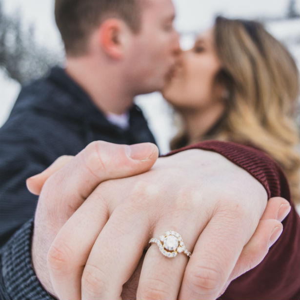 woman kissing fiance wearing unique halo engagement ring