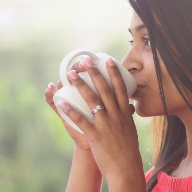 woman sipping coffee wearing a one carat diamond ring