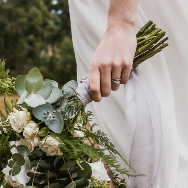 woman wearing emerald cut three stone engagement ring holding bouquet