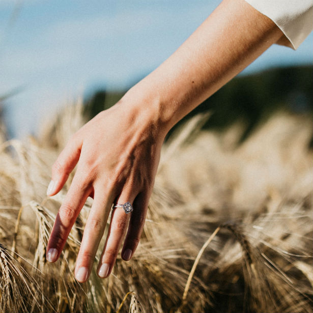 woman wearing engagement ring running hand through wheat