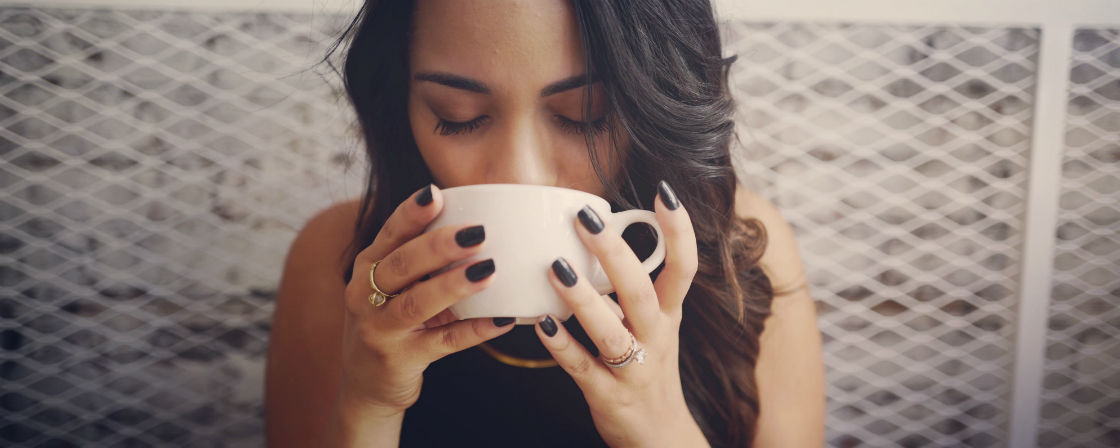 woman wearing engagement ring sipping from cup