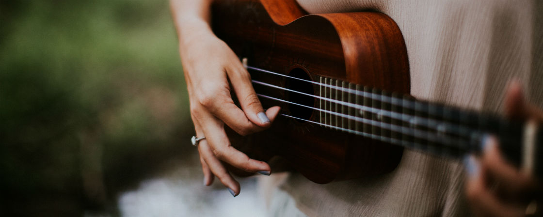 woman wearing low profile engagement ring and playing guitar