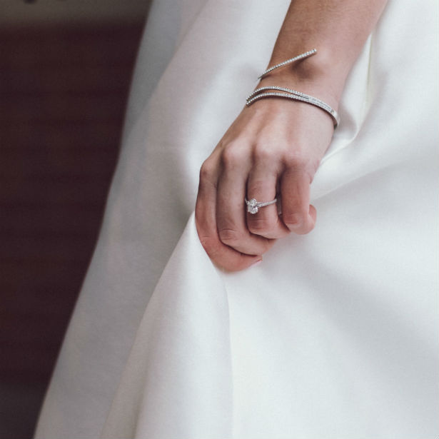 woman wearing oval engagement ring holding dress
