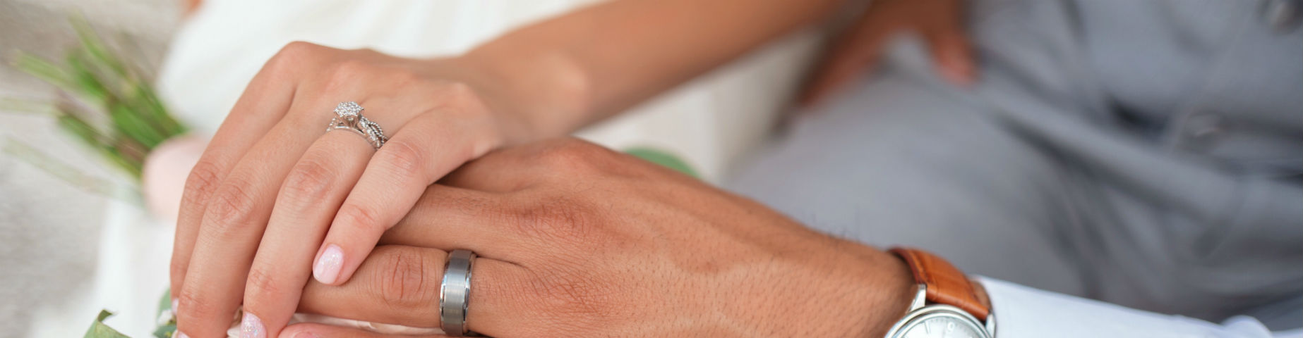woman wearing vintage style engagement ring with her hand on top of husband's