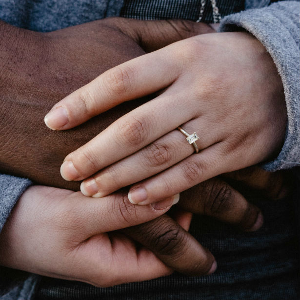 woman wearing yellow gold emerald cut engagement ring holding man's hand