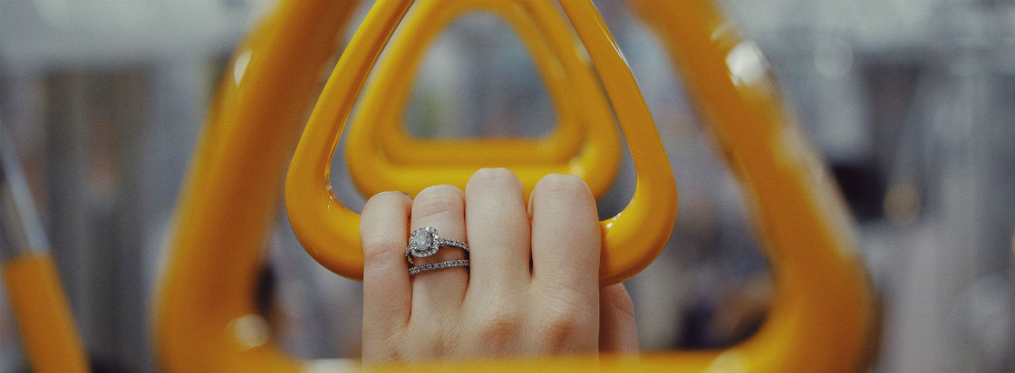 woman's hand holding metro handle wearing engagement ring