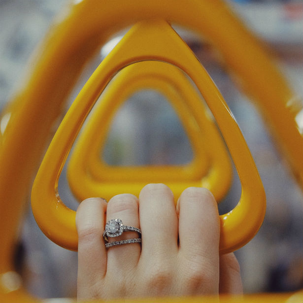 woman's hand holding metro handle wearing engagement ring: wearing engagement and wedding ring in public