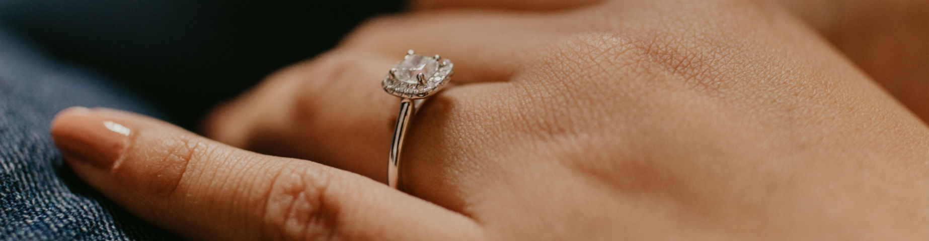woman's hand wearing halo engagement ring