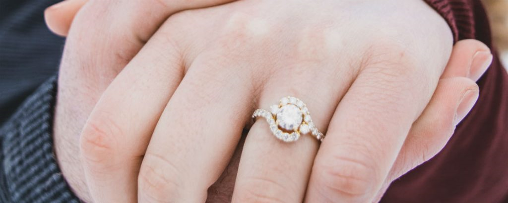 woman's hand wearing unique halo engagement ring